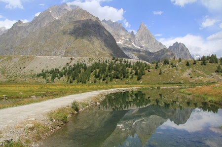 aosta: Reflection of Aiguille noire mountain in Combal lake . Val Veny in Aosta valley close to french border.