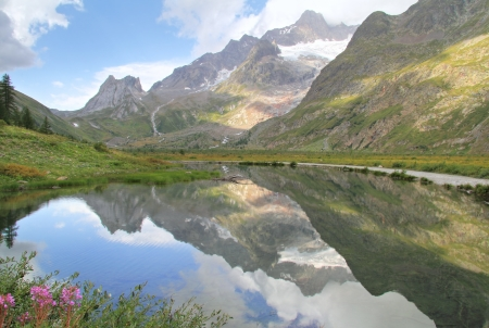 aosta: Alpine landscape reflected  in Combal lake with Col de la Seine in the distance . Courmayeur alps near french border