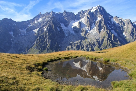 Grand Jorasses ices and Giant's tooth peak reflected in alpine pond from Mont de la Saxe high mountain trail . Val Ferret , Courmayeur , Italy photo
