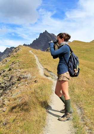 Young woman on mountain trail watching with binoculars . Adventure and outdoor conceptual Standard-Bild