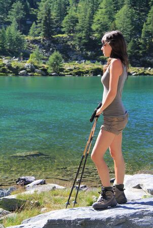 aosta: Hiking girl rests looking at green beautiful Arpy lake  Alpine mountains in Aosta valley