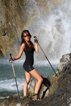 waterfall model: Hiking model poses under beautiful mountain waterfall. Water creates natural rainbow colors arch .