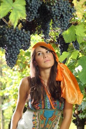 gitana: Hermosa chica vestida de gitana uvas retrato estilo y viñedo como fondo