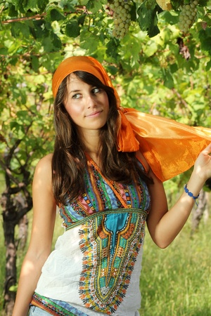 gipsy: Beautiful girl dressed gypsy style in a vineyard with red and green grapes