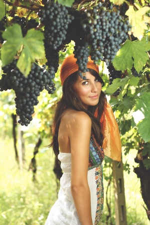 gipsy: Beautiful girl dressed like a gypsy poses in a vineyard with grapes all around