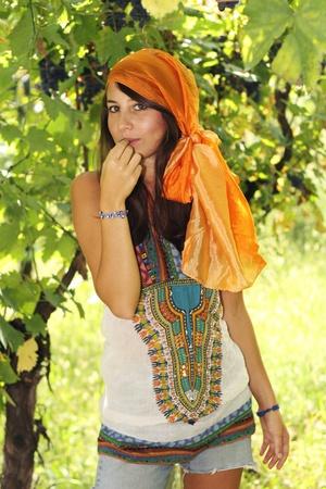 gitana: Muchacha hermosa en un viñedo come un grapeberry vestido de gitana