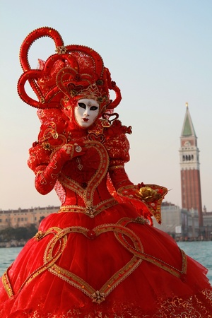 Red venice carnival dress with heart shaped fabrics  San Marco Bell tower in background