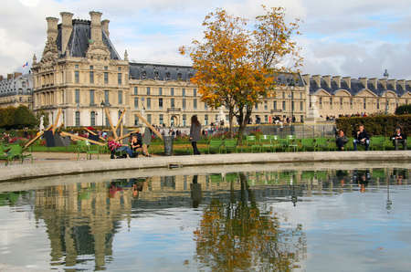 People relaxing at Tuileries park , seating by the pond . Reflection of palace