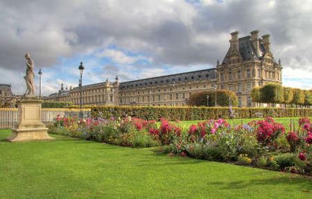 Tuileries gardens in Paris , Louvre museum. Royal gardens and cloudscape Editorial