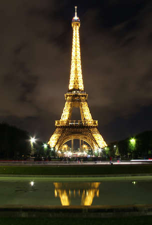 Famous Eiffel Tower lighted at night and reflected in a pond   Paris , France