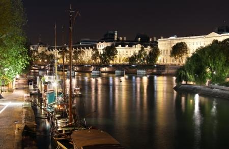 Los muelles del Sena y barcos iluminados con el Museo del Louvre en Par�s por la noche bakground Foto de archivo - 15841745