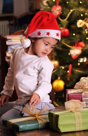 Beautiful little child stares at her Christmas gifts. Kid is wearing a xmas hat Standard-Bild