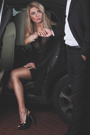 Beautiful blonde girl and gentleman helping her to get out from a car . Elegant and fashion concept