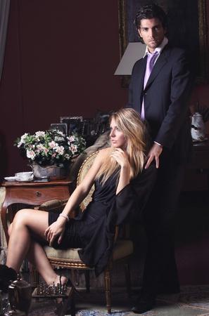 parejas sensuales: Retrato de una pareja de moda en clave baja. El hombre se pone de pie y mira a la cámara Foto de archivo