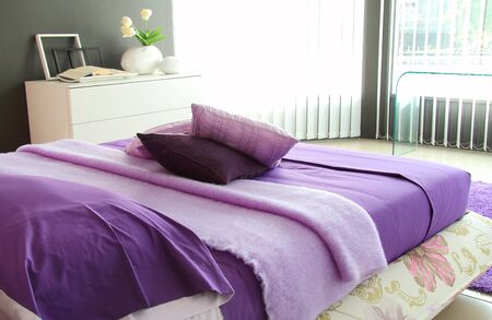 Purple bedroom in strong morning light through window photo