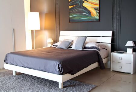 Modern stylish bedroom . Light from a warm lamp  photo