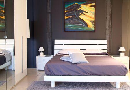 Modern stylish bedroom  in warm light. Mirror on left side photo