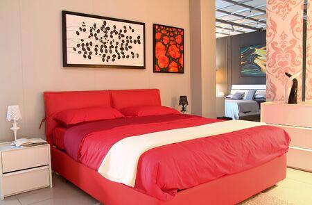 Modern design bedroom. Red  bed inside furniture store . Warm back light  Standard-Bild