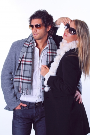 Couple of fashion models wearing sunglasses and winter dress.  photo