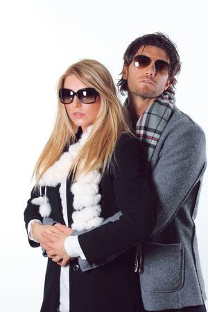 Couple of fashion models wearing winter dress and sunglasses. Model looks at camera photo