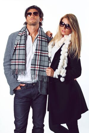 Couple of fashion models wearing sunglasses and winter dress. Bold expressions photo