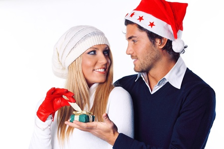 Beautiful blonde girl receives and opens her  christmas gift . Girl lovely looks to her boyfriend photo