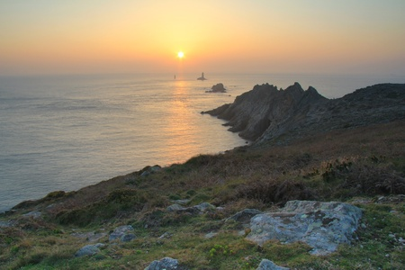 Famous Pointe du Raz in Brittany at sunset . Silhouette of the lighthouse. Phare de la vieille.