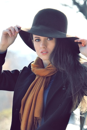 Beautiful portrait of a very attractive girl posing outdoor with an hat photo