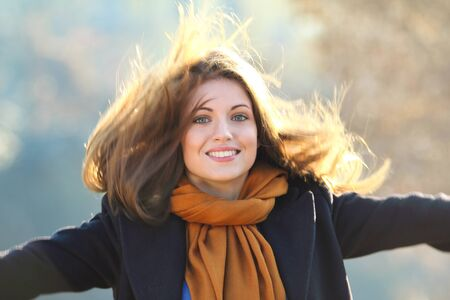 attractive gorgeous: Beautiful smiling girl with long hairs in motion against warm sun light Stock Photo