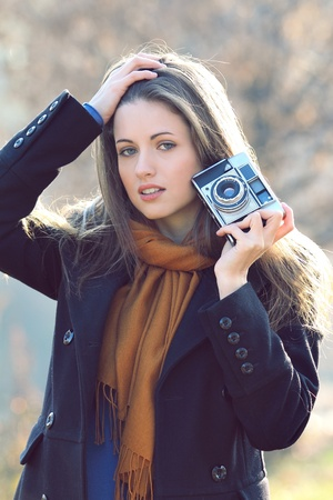 Outdoor shot in natural light of a beautiful girl in fashion pose . Vintage camera in one hand photo
