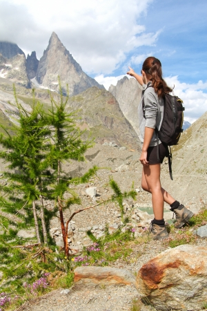 noire: Trekking girl on high mountain trail pointing at the Aiguille Noire peak in Aosta Valley , Italy. Mountain and outdoor conceptual