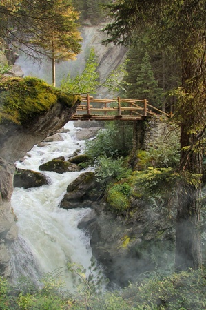 suspend: Wooden bridge suspended over mighty waterfall in a fairy misty forest