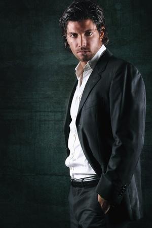 Drama light on handsome model in elegant dress . Dark textured background