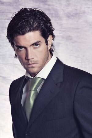 Elegant and stylish male model in black dress and green tie . Studio shot with textured backdrop Standard-Bild