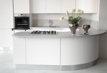 Modern white kitchen with open oven  and steel sink. Stylish and elegant flowers decoration