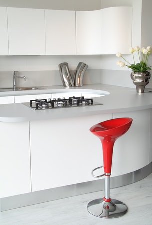 Modern white kitchen with stylish and elegant red stool .