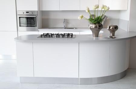 Modern white kitchen with closed oven . Stylish and elegant flowers decoration Standard-Bild