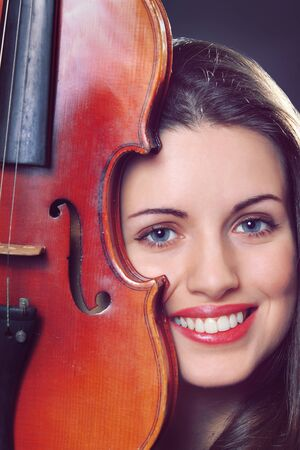 Beautiful girl portrait with a violin detail   Model is smiling photo
