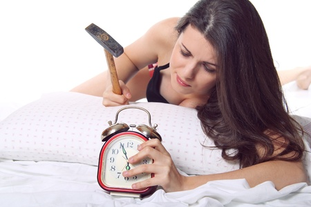 Beautiful girl in bed ready to break the alarm clock with an hammer photo