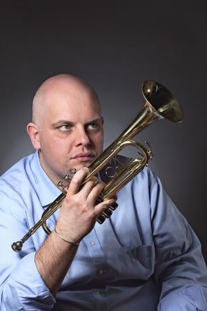 gaze: Man kijkt naar zijn trompet met een diepe blik. Grijze achtergrond portret