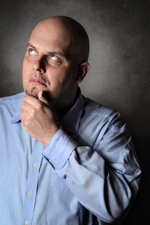 dubious: Man with pensive expression deeply thinking . Portrait with grey textured background