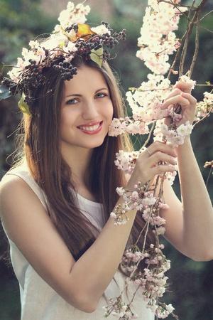 Portrait of a beautiful nymph among cherry flowers photo