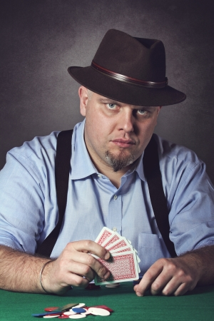 Man at the green table playing poker and looks at camera. Stock Photo - 19341748