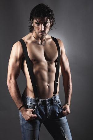 sexy man: Sexy man shirtless with black suspenders and bold expression . Grey backdrop portrait Stock Photo