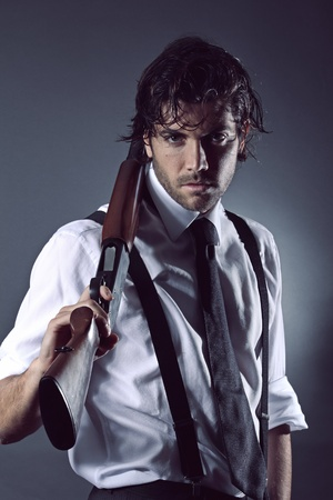 gangsters: Handsome man dressed like a gangster posing with shotgun  Grey backdrop portrait