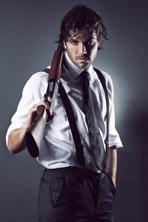 Knappe mannequin gekleed als een gangster poseren met jachtgeweer Grijze achtergrond portret Stockfoto