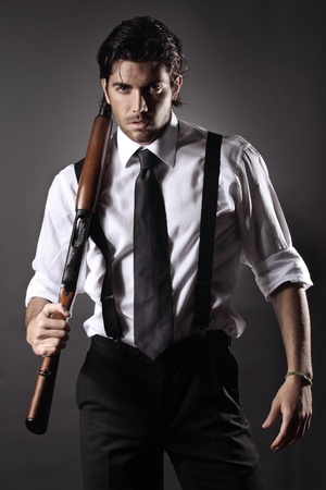 Very attractive fashion model dressed like a gangster with shotgun Grey backdrop portrait