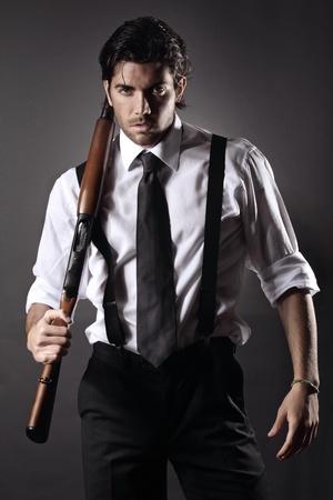 Zeer aantrekkelijk fashion model gekleed als een gangster met een shotgun Grey achtergrond portret Stockfoto