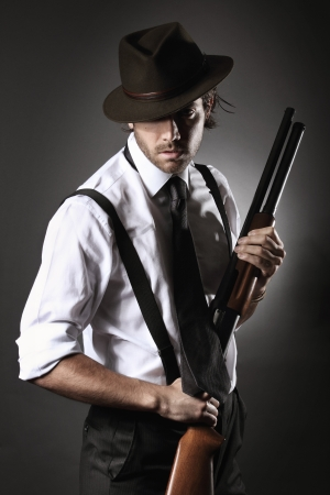 Fashion model dressed like a gangster poses with shotgun and hat