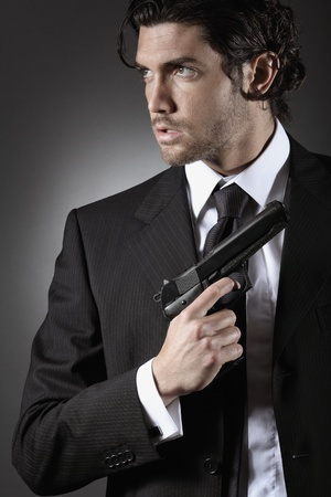 銃を持つハンサムなスパイの肖像画。シークレット エージェントまたはボディー ガードの概念